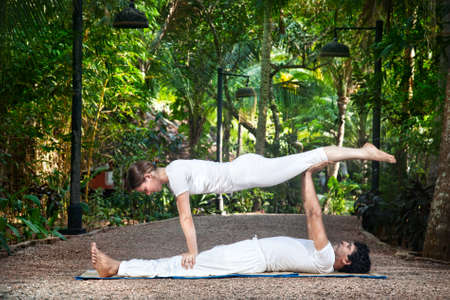 ashtanga: man and woman doing acroyoga in white cloth in the garden