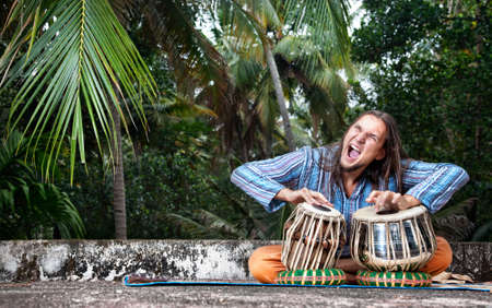Man playing on traditional Indian tabla drums at tropic background  photo