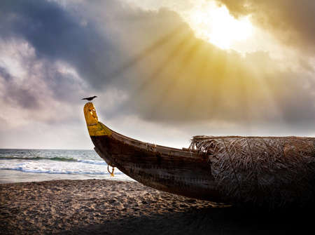 Fishing boat on the beach with crow on it near the ocean at dramatic cloudy sunset sky background   photo
