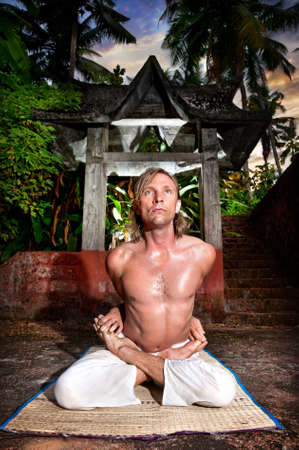 padmasana: Yoga meditation in baddha padmasana pose by man in white trousers at stone temple background in tropical forest