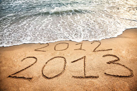 2013 year on the sand beach near the ocean. 2012 is been erasing by wave Stock Photo - 13844866