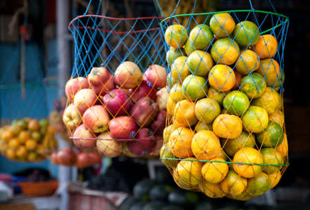 Various Indian oranges and apples in bags at the market, Kumly, Kerala, India  photo