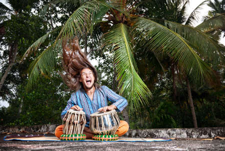 Man with hair up playing on traditional Indian tabla drums at palm trees background  photo