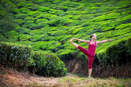 Yoga utthita Hasta Padangustasana one leg balance pose by woman in red cloth on tea plantations in Munnar hills, Kerala, India