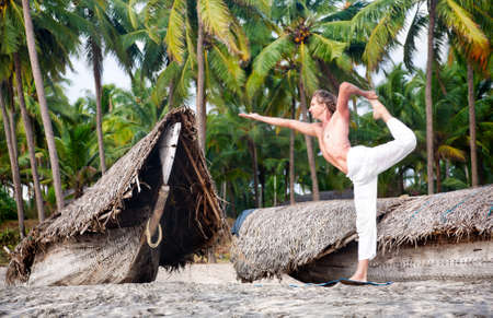 Yoga natarajasana dancer pose by fit man in white trousers on the beach near the fishermen boats in Varkala, Kerala, India photo