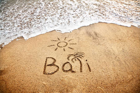 bali: Bali title with sun and palm drawing on the sand beach near the ocean