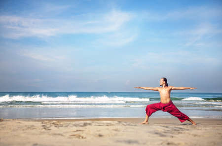 Yoga virabhadrasana II warrior pose by fit man with long hair in red trousers on the beach at ocean background Stock Photo - 13982535
