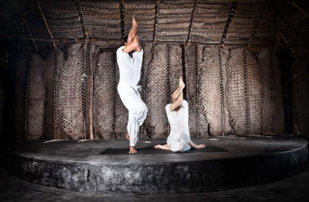 Couple yoga of woman and man doing sitting and standing garudasana in white cloth in yoga hall, Varkala, Kerala, India photo