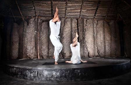 Couple yoga of woman and man doing sitting and standing garudasana in white cloth in yoga hall, Varkala, Kerala, India photo