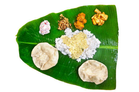 Indian traditional vegetarian thali from rice, dal, potatoes, tomato salad and two puri on banana leaf isolated on white background. Free space for text  photo