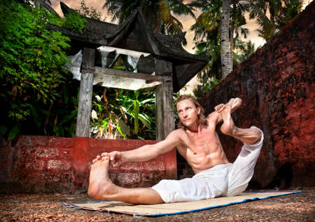 dhanurasana: Yoga akarna dhanurasana archer pose by man in white trousers near stone temple at sunset background in tropical forest  Stock Photo
