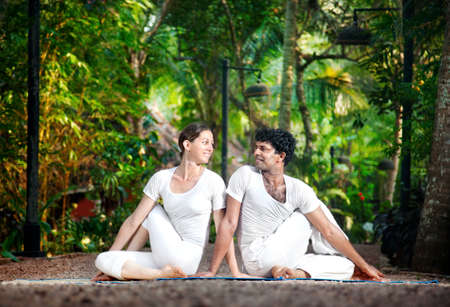 Couple Yoga of man and woman in white cloth doing matsyendrasana spinal twist pose looking at each other and smiling in the garden photo