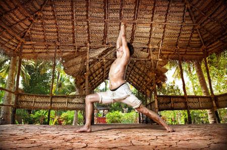 hatha: Yoga virabhadrasana I warrior pose by fit man in white trousers on the drought earth in yoga shala, Varkala, Kerala, India Stock Photo