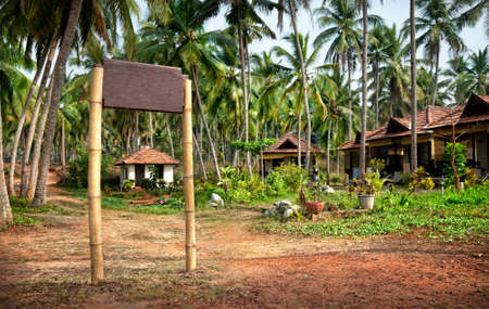 Cottages and bamboo signboard with free space for your text in palm tree forest in Varkala, Kerala, India photo