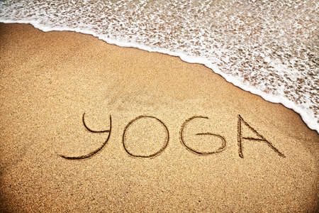 yoga sunset: Yoga title on the sand beach near the ocean Stock Photo
