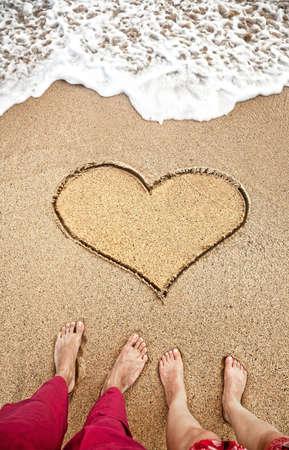 piernas hombre: Piernas de joven pareja de pie en la playa cerca del coraz�n en la arena con el oc�ano cerca de