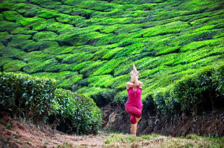 Yoga garudasana eagle pose by woman in red cloth on tea plantations in Munnar hills, Kerala, India photo