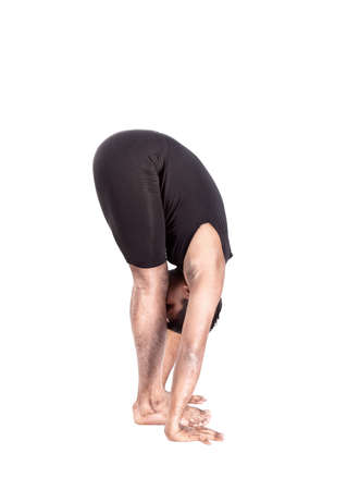 bending forward: step of surya namaskar, sun salutation Exercise by Indian man in black cloth at white background