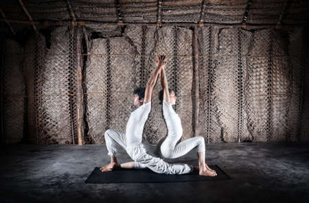 Couple yoga of woman and man doing ashwa sanchalanasana lunge pose in white cloth in yoga hall, Varkala, Kerala, India photo