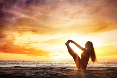 Yoga naukasana boat pose by young woman with long hair on the beach near the ocean at dramatic sunset background