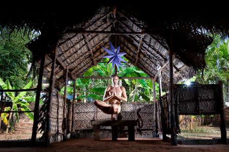 baddha: Yoga Ardha Baddha Padma Padangusthasana balancing on toes pose by fit man in yoga hall at banana trees background in Varkala, Kerala, India