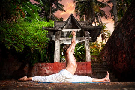 Yoga hanumanasana monkey pose by man in white trousers near stone temple in tropical forest  photo