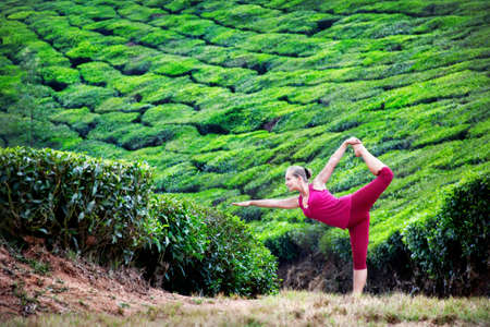 Yoga natarajasana dancer pose by woman in red cloth on tea plantations in Munnar hills, Kerala, India photo