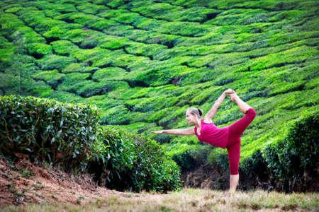 Yoga natarajasana dancer pose by woman in red cloth on tea plantations in Munnar hills, Kerala, India photo