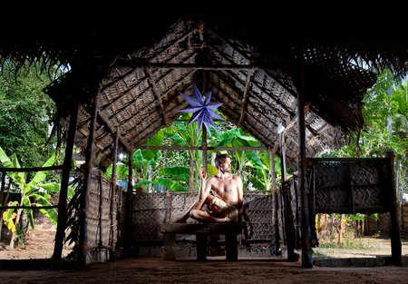 dhyana: Yoga Matsyendrasana torsione pongono l'uomo in forma, nel padiglione yoga a sfondo alberi di banane in Varkala, Kerala, India