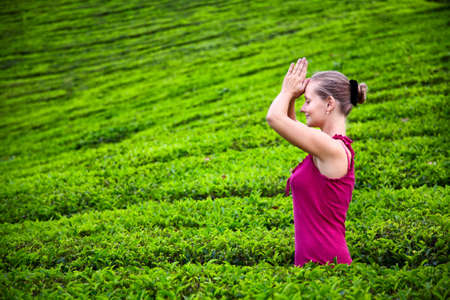 namaste: Orar mujer con las manos en Namaste en tela roja en las plantaciones de t� en las colinas Munnar, Kerala, India