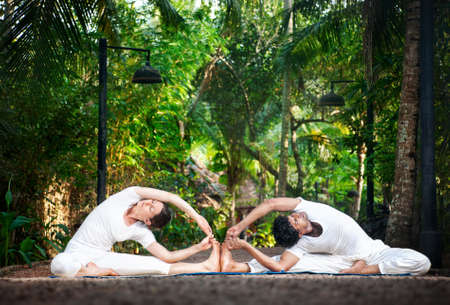 Couple Yoga of man and woman in white cloth doing parivrtta janu sirsasana Revolved Head to Knee pose in the garden photo