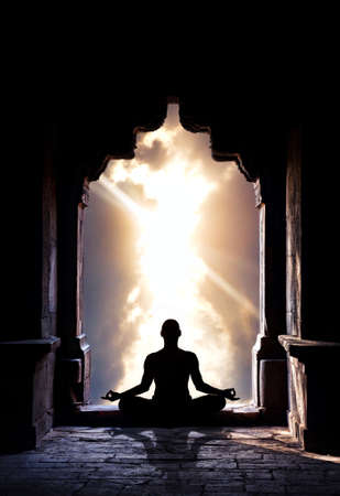 inner peace: Yoga meditation in lotus pose by man silhouette in old temple arch at dramatic sky background. Free space for text