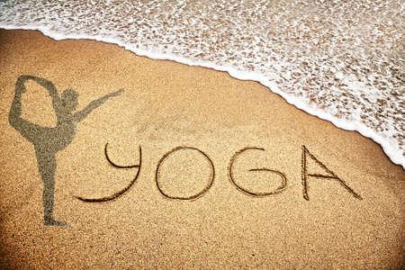 asana: Yoga title with man doing yoga on the sand beach near the ocean Stock Photo