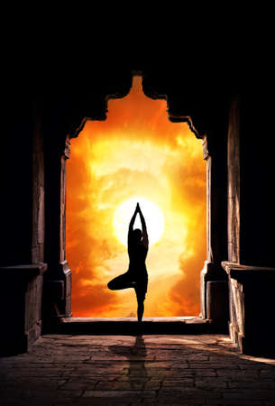 Yoga vrikshasana tree pose by man silhouette in old temple arch at dramatic sunset sky background. Free space for text photo