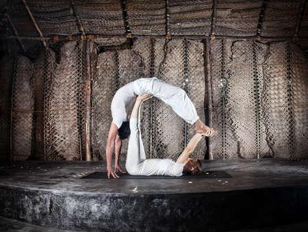 Acro yoga de la mujer y el hombre en un paño blanco en el yoga sala, Varkala, Kerala, India
