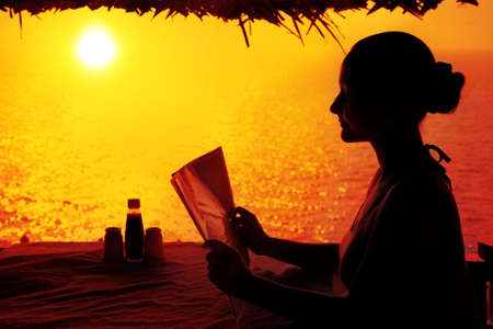 Young woman in restaurant looking at menu in Varkala, Kerala, India photo