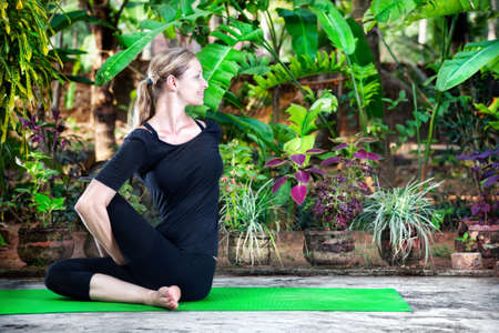 hatha: Yoga twisting pose by young woman in black cloth in the garden with banana trees and tropical plants in the pots Stock Photo
