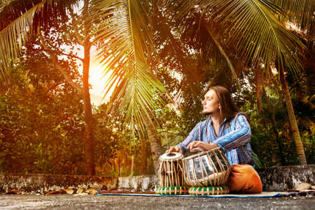 inner peace: Man playing on traditional Indian tabla drums at sunset tropic background