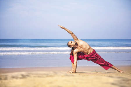 Yoga utthita, Parsvakonasana pose by fit man with long hair in red trousers on the beach at ocean background  photo