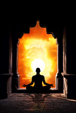 chakra: Yoga meditation in lotus pose by man silhouette in old temple arch at orange sunset sky background