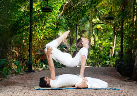 two minds: man and woman doing acroyoga in white cloth in the garden