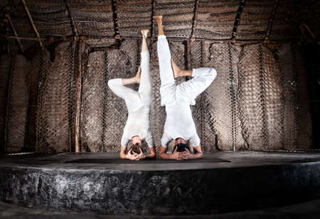 yoga of woman and man doing shirshasana headstand in white cloth in yoga hall, Varkala, Kerala, India photo