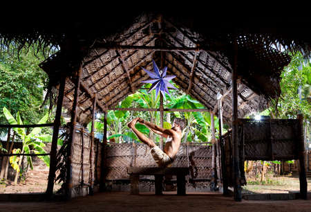 Yoga naukasana boat pose by man in white trousers in yoga hall at banana trees background in Varkala, Kerala, India    photo