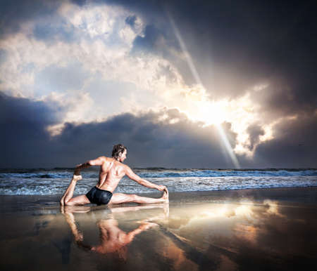eka: Yoga eka pada raja kapotasana pigeon pose by man on the beach near the ocean at sunset background