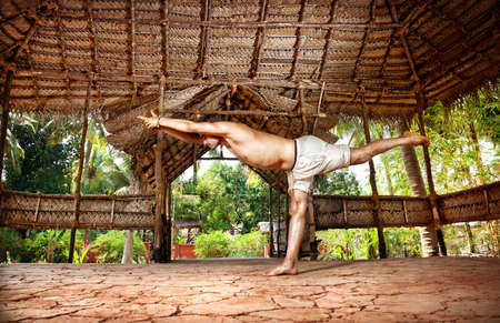 iii: Yoga virabhadrasana III warrior pose by fit man in white trousers on the drought earth in yoga shala, Varkala, Kerala, India