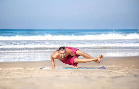 Yoga astavakrasana eight angle pose by fit man with long hair in red trousers on the beach at ocean background  photo