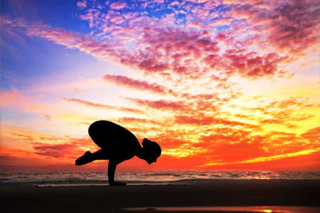 Yoga bakasana crane pose by woman in silhouette with dramatic sunset sky background. Free space for text photo