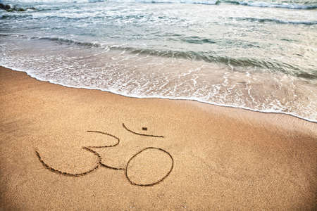 spiritual journey: Om symbol on the sand at the beach near the ocean Stock Photo