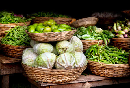 Various different vegetables and mango in wooden baskets at the market, Kumly, Kerala, India  photo