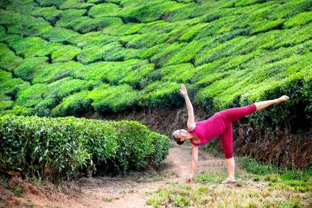 chandrasana: Yoga ardha chandrasana half moon pose by woman in red cloth on tea plantations in Munnar hills, Kerala, India